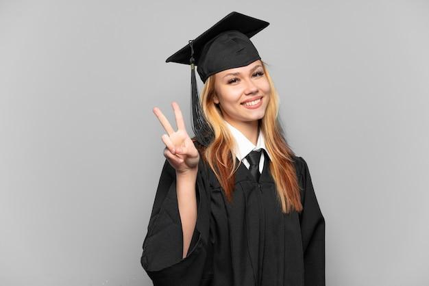 Joven graduada universitaria aislado fondo sonriendo y mostrando el signo de la victoria