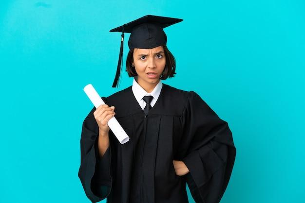Joven graduada universitaria sobre fondo azul aislado enojado