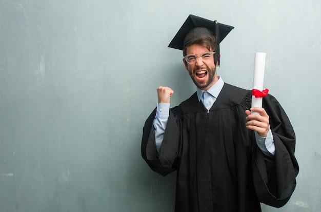 Joven graduado contra una pared de grunge con un espacio de copia muy feliz y emocionado