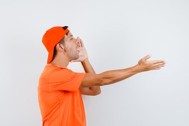 Joven gritando a alguien con camiseta naranja y gorra.