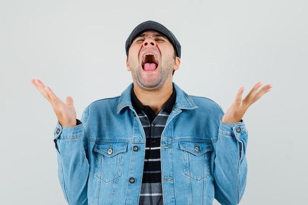 Joven gritando mientras levanta las manos en camiseta, chaqueta, gorra y luce feliz, vista frontal.