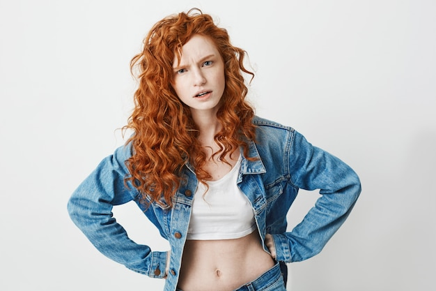 Joven grosera con el pelo rizado rojo brutalmente con los brazos en jarras.