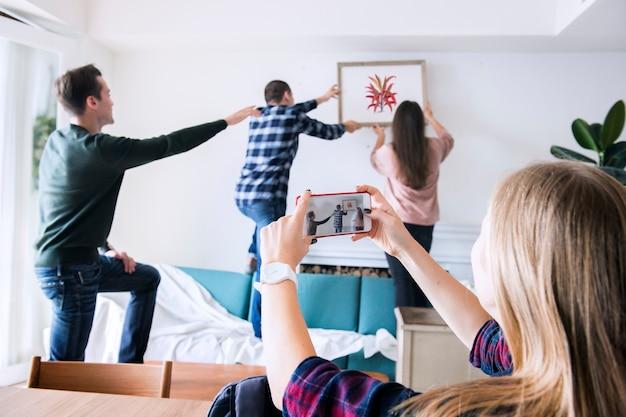 Joven grupo de amigos decorando el apartamento y una mujer tomando una foto.