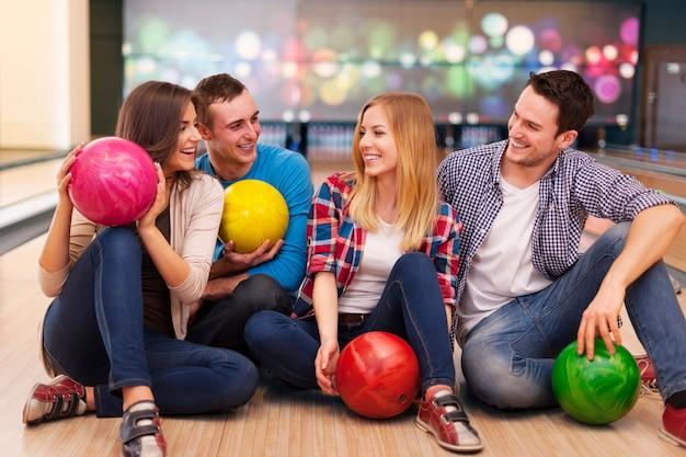 Joven grupo de amigos se divierten en la bolera