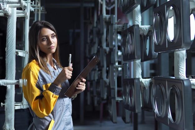 Una joven guapa y blanca trabaja en el taller de pintura de la planta, revisa los productos metálicos sin pintar y registra en la lista de verificación.