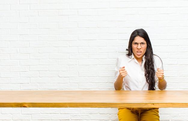 Joven y guapa mujer latina gritando agresivamente con mirada molesta, frustrada, enojada y puños apretados, sintiéndose furiosa sentada frente a una mesa