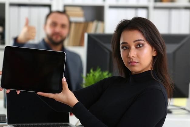 Joven y guapa mujer morena en oficina sostenga tableta en manos