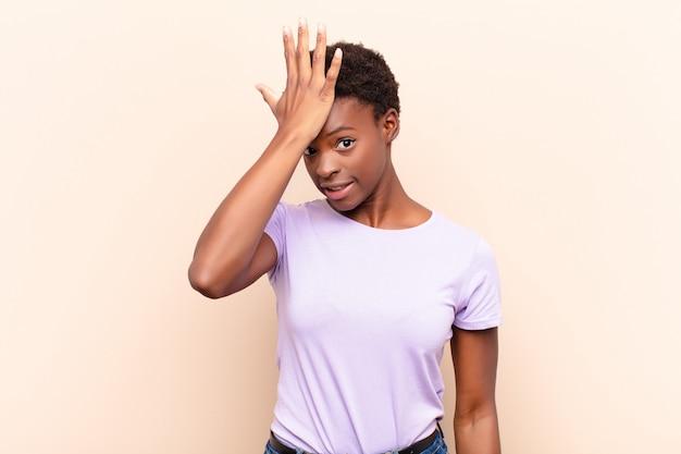 Joven y guapa mujer negra levantando la palma de la mano a la frente pensando, vaya, después de cometer un estúpido error o recordar, sentirse tonta