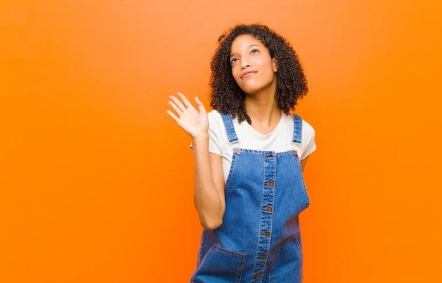 Joven y guapa mujer negra sonriendo feliz y alegremente, saludando con la mano, dándole la bienvenida y saludando, o diciéndole adiós contra la pared naranja