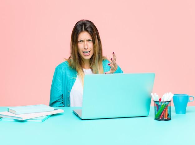 Joven y guapa mujer que trabaja con una computadora portátil que parece enojada, molesta y frustrada gritando wtf o qué te pasa
