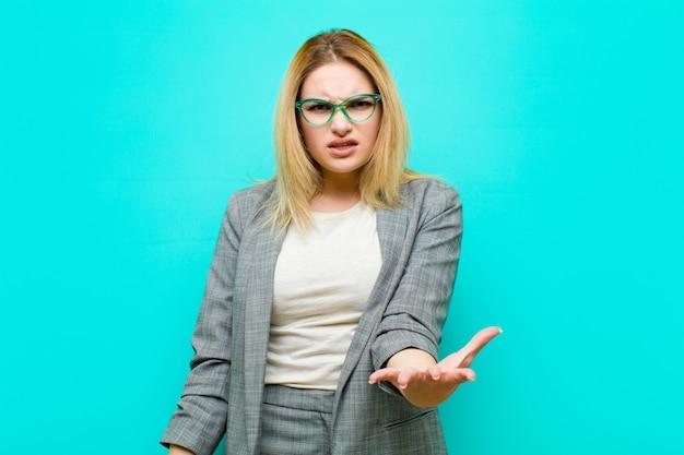 Joven y guapa mujer rubia que parece enojada, molesta y frustrada gritando wtf o lo que te pasa contra la pared plana