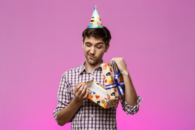 Joven guapo abriendo regalo de cumpleaños sobre pared púrpura.
