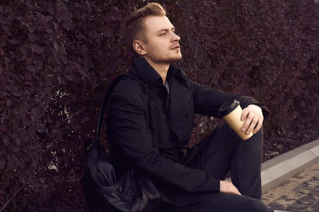 Joven guapo en abrigo oscuro con taza de café