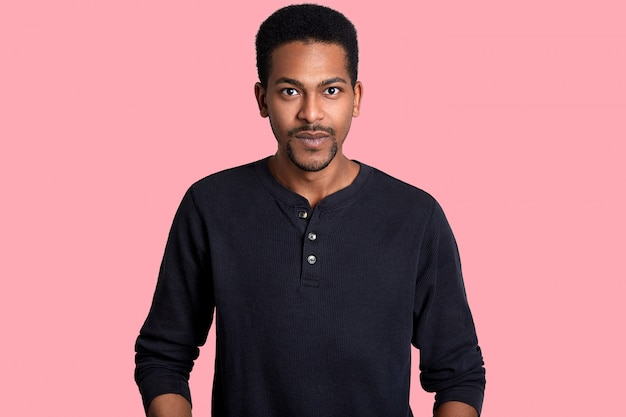 Joven guapo africano lleva camisa negra en rosa. el hombre se ve feliz, tiene una idea nueva e interesante.