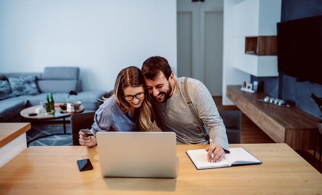 Joven guapo alegre pareja caucásica en el amor sentado en la mesa de comedor y usando la computadora portátil para ir de compras en línea mientras abrazaba. mujer con tarjeta de crédito.