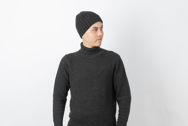 Joven guapo asiático vistiendo suéter gris y gorro pensando en una idea mientras mira hacia arriba