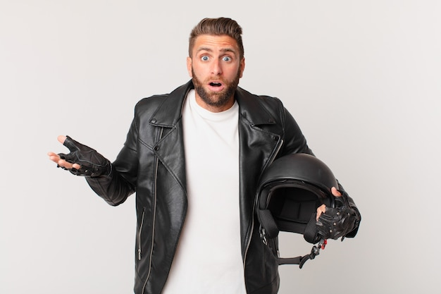Joven guapo asombrado, conmocionado y asombrado con una sorpresa increíble. concepto de casco de moto