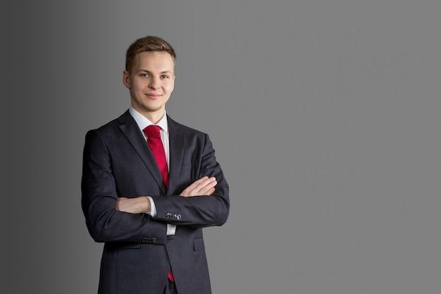Joven guapo, atractivo hombre rubio con traje y corbata roja en la pared gris