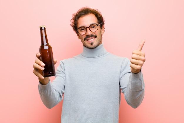 Joven guapo bailando con una cerveza contra la pared plana rosa