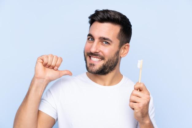 Joven guapo con barba cepillando sus dientes sobre pared aislada orgulloso y satisfecho de sí mismo