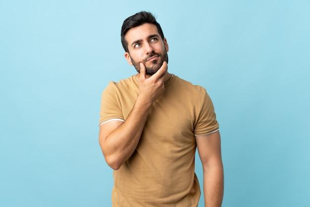 Joven guapo con barba sobre pared aislada teniendo dudas