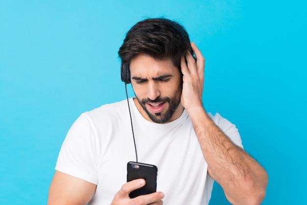 Joven guapo con barba sobre pared azul aislada escuchando música con un móvil y cantando