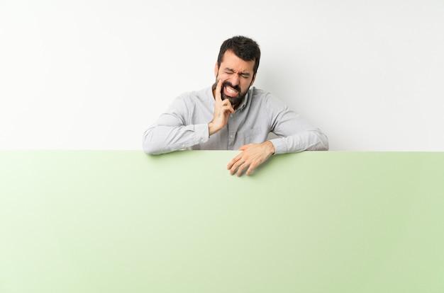 Joven guapo con barba sosteniendo un gran cartel verde vacío con dolor de muelas