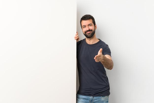 Joven guapo con barba sosteniendo una gran pancarta vacía estrechándole la mano para cerrar un buen negocio