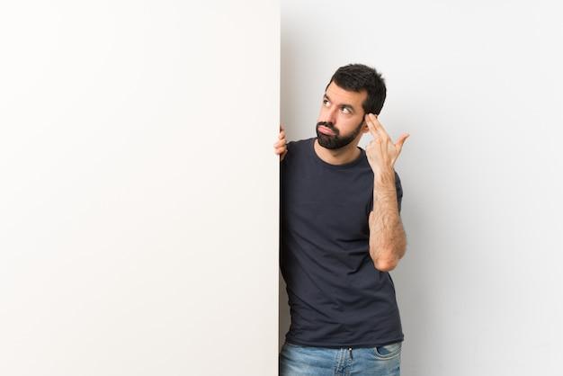 Joven guapo con barba sosteniendo una gran pancarta vacía con problemas para hacer el gesto de suicidio