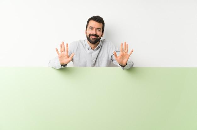 Joven guapo con barba sosteniendo una gran pancarta vacía verde contando diez con los dedos