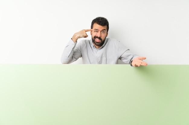 Joven guapo con barba sosteniendo una gran pancarta verde vacía haciendo el gesto de locura poniendo el dedo en la cabeza