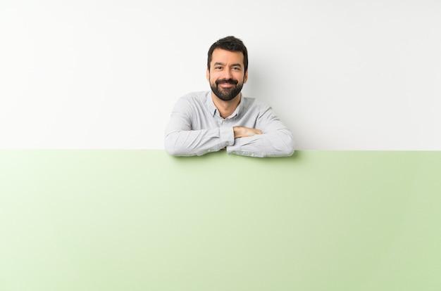 Joven guapo con barba sosteniendo una gran pancarta verde vacía manteniendo los brazos cruzados en posición frontal