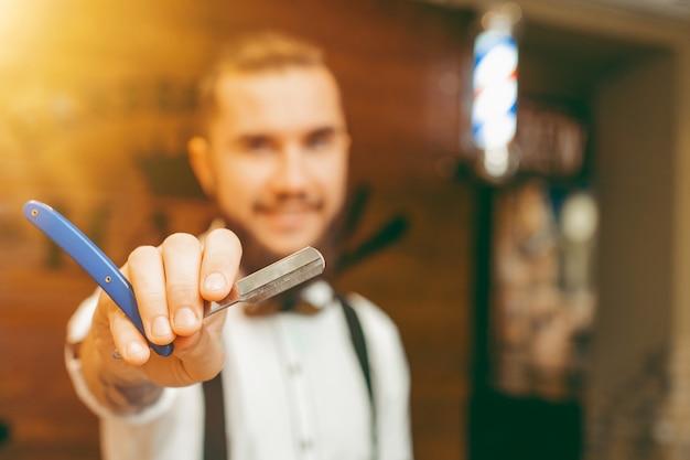Joven guapo barbero barbudo con una navaja en la mano