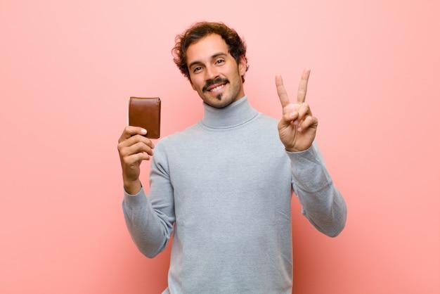 Joven guapo con una billetera contra la pared plana rosa