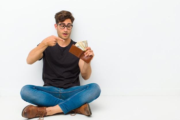 Joven guapo con una billetera sentada en el piso