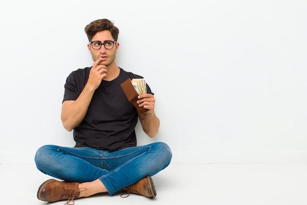 Joven guapo con una billetera sentada en el suelo sentada en el suelo en una habitación blanca