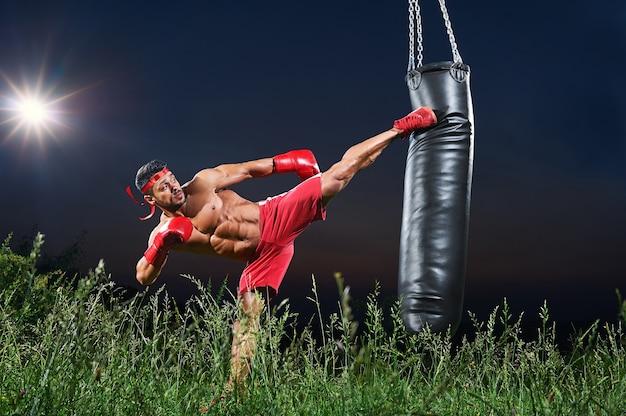 Joven guapo boxeador macho practicando habilidades en la noche