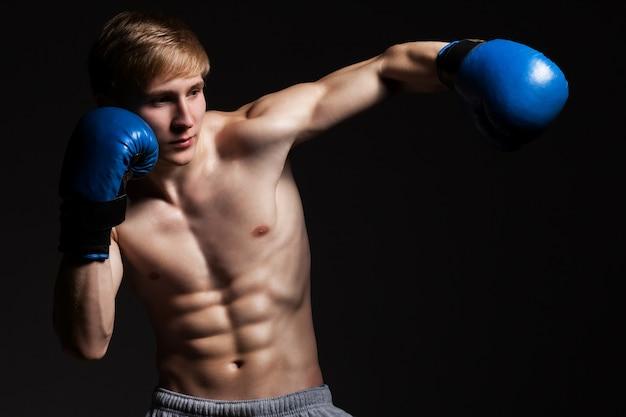 Joven guapo boxeador en un movimiento