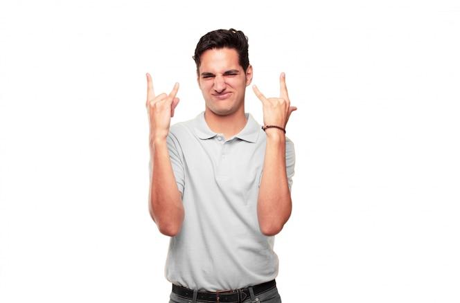 Joven guapo bronceado cantando rock, bailando, gritando, gesticulando de una manera rebelde, enojado.