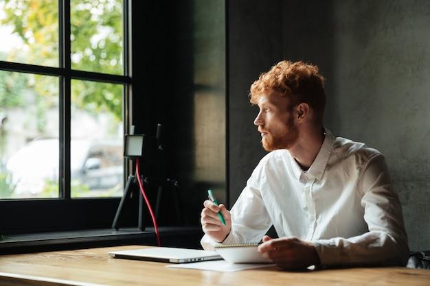 Joven guapo con cabeza lectora barbudo sentado en el lugar de trabajo en casa, mirando a la ventana grande
