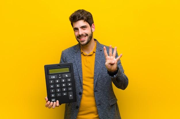 Joven guapo con una calculadora sobre fondo naranja
