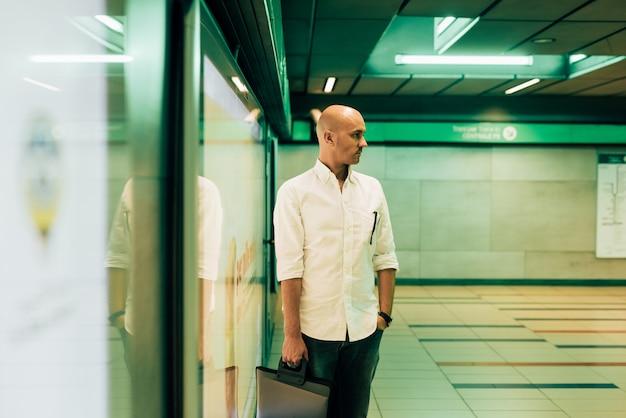 Joven guapo calvo empresario caucásico esperando el tubo en la estación de metro