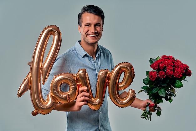 Joven guapo con camisa azul está de pie con rosas rojas y globo de aire etiquetado como amor en la mano en gris.
