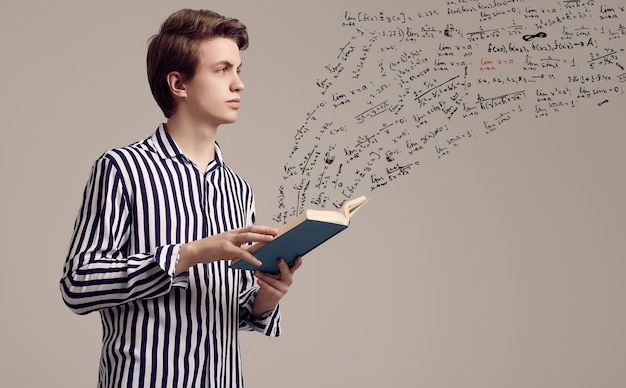 Joven guapo en camisa a rayas leyendo un libro sobre fondo gris