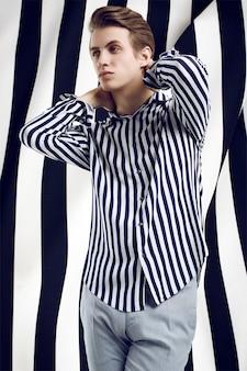 Joven guapo en camisa a rayas plantea en blanco y negro