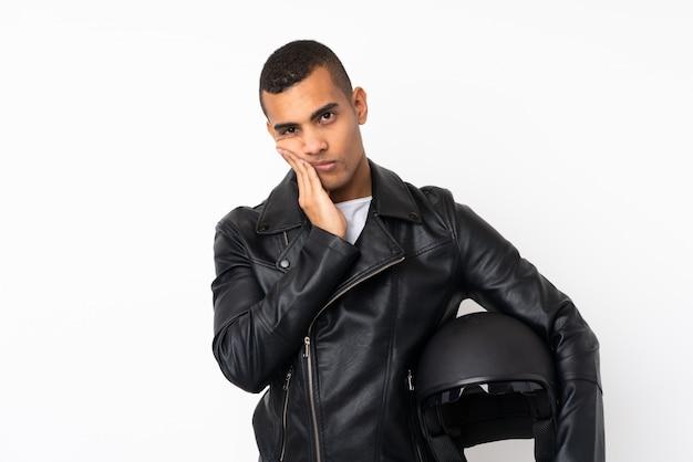 Joven guapo con un casco de moto sobre pared blanca aislada infeliz y frustrado