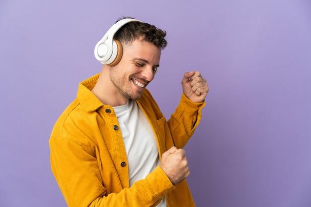 Joven guapo caucásico aislado escuchando música y bailando
