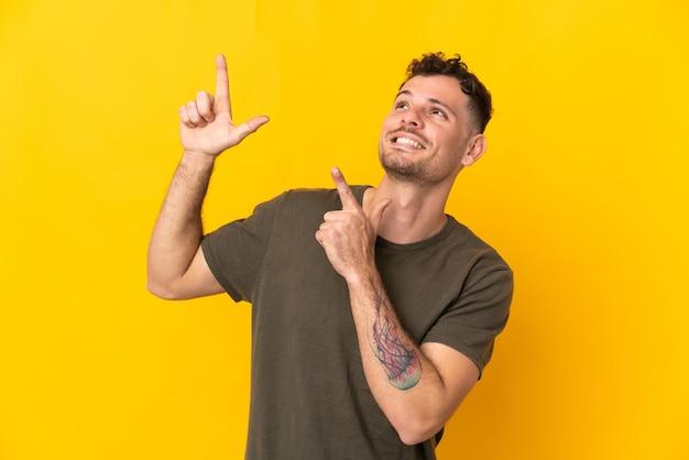 Joven guapo caucásico aislado en la pared amarilla apuntando con el dedo índice una gran idea