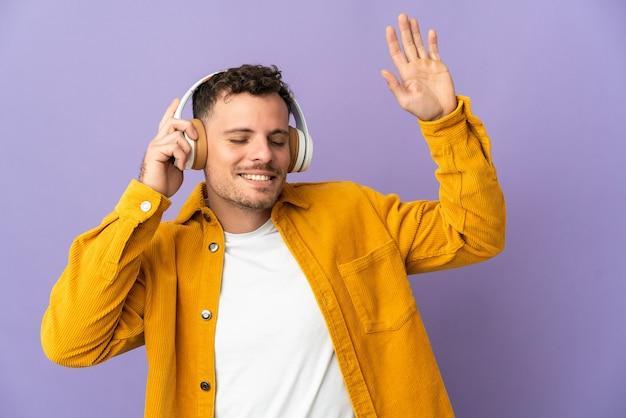 Joven guapo caucásico aislado en púrpura escuchando música y bailando