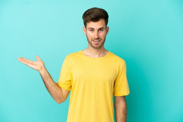 Joven guapo caucásico aislado sobre fondo azul sosteniendo copyspace imaginario en la palma para insertar un anuncio